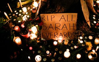 LONDON, UNITED KINGDOM - MARCH 13: Candles burn at the base of a tree as mourners for the life of murdered 33-year-old Sarah Everard, whose remains were found this week in woodland in Kent, disperse from an officially cancelled 'Reclaim These Streets' vigil on Clapham Common in London, United Kingdom on March 13, 2021. Wayne Couzens, a serving Metropolitan Police officer, was yesterday charged with the kidnap and murder of Ms Everard, who went missing over a week ago from south London and whose disappearance and death has seen women across the country speaking up about their own fears of not being safe on the streets. (Photo by David Cliff/Anadolu Agency via Getty Images)