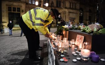 NOTTINGHAM, ENGLAND - MARCH 13: A female police officer lights a candle next to a makeshift memorial during a vigil for Sarah Everard, following her kidnap and murder, on March 13, 2021 in Nottingham, England. Vigils are being held across the United Kingdom in memory of Sarah Everard. Yesterday, the Police confirmed that the remains of Ms Everard were found in a woodland area in Ashford, a week after she went missing as she walked home from visiting a friend in Clapham. Metropolitan Police Officer Wayne Couzens has been charged with her kidnap and murder. (Photo by Nathan Stirk/Getty Images)
