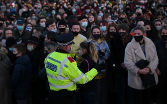 A police officer asks well-wishers not to linger and to move on as they gather at the band-stand where a planned vigil in honour of murder victim Sarah Everard, which was officially cancelled due to Covid-19 restrictions, was to take place on Clapham Common, south London on March 13, 2021, - The police officer charged with murdering young Londoner, Sarah Everard, who disappeared while walking home from a friend's house, appeared in court on March 13, 2021, as organisers cancelled a vigil in her honour due to coronavirus restrictions. (Photo by JUSTIN TALLIS / AFP) (Photo by JUSTIN TALLIS/AFP via Getty Images)