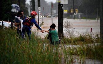 """A rescue worker helps residents cross a flooded road during heavy rain in western Sydney on March 20, 2021, amid mass evacuations being ordered in low-lying areas along Australia's east coast as torrential rains caused potentially """"life-threatening"""" floods across a region already soaked by an unusually wet summer. (Photo by Saeed KHAN / AFP) (Photo by SAEED KHAN/AFP via Getty Images)"""