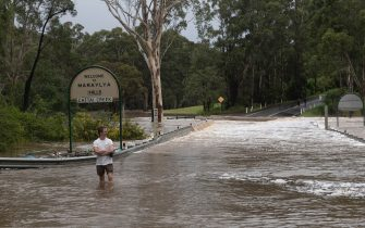 MARAYLYA, AUSTRALIA - MARCH 20: A person walks through fast moving flood waters at Cattai Creek on March 20, 2021 in Maraylya, Australia. Heavy rain and flooding has trigger evacuations on the New South Wales mid coast with over 120mm rain expected for Sydney and residents urged to stay at home. (Photo by Brook Mitchell/Getty Images)