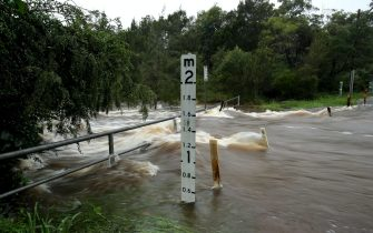 epa09084882 Oxford Falls Road is closed due to flooded on the Northern Beaches in Sydney, Australia, 20 March 2021. More rain is forecast for the New South Wales coast and other parts of the state, with flood warnings in place and the premier advising residents to stay home.  EPA/BRENDON THORNE AUSTRALIA AND NEW ZEALAND OUT
