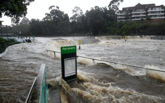 epa09084883 The swollen Parramatta river is seen breaking it s banks at the Charles St weir and ferry wharf, at Parramatta in Sydney, Australia, 20 March 2021. More rain is forecast for the New South Wales coast and other parts of the state, with flood warnings in place and the premier advising residents to stay home.  EPA/DAN HIMBRECHTS AUSTRALIA AND NEW ZEALAND OUT