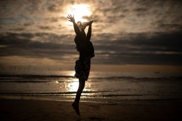 LIVERPOOL, UNITED KINGDOM - AUGUST 21:  A young muslim girl dances and runs in the sea as she and her family celebrate Eid Al-Adha by watching the sunset at Crosby beach on August 21, 2018 in Liverpool, England. The traditional four-day celebratory festival marks one of the holiest days in the Islamic religious calendar.  (Photo by Christopher Furlong/Getty Images)