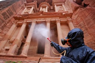 TOPSHOT - A labourer sprays disinfectant in Jordan's archaeological city of Petra south of the capital Amman on March 17, 2020, to prevent the spread of COVID-19. (Photo by Khalil MAZRAAWI / AFP) (Photo by KHALIL MAZRAAWI/afp/AFP via Getty Images)