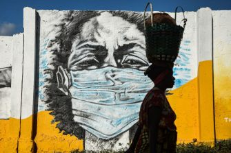 TOPSHOT - A Tanzanian woman carries a basket on her head as she walks in front of a graffiti painted by the Wachata artists group to raise awareness about wearing masks to avoid the risk of the COVID-19 coronavirus in Dar es Salaam on May 26, 2020. (Photo by Ericky BONIPHACE / AFP) / RESTRICTED TO EDITORIAL USE - MANDATORY MENTION OF THE ARTIST UPON PUBLICATION - TO ILLUSTRATE THE EVENT AS SPECIFIED IN THE CAPTION (Photo by ERICKY BONIPHACE/AFP via Getty Images)