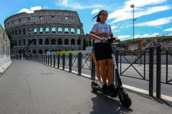 Youth ride a shared electric scooter on June 22, 2020 near the Coliseum monument in Rome, as the country eases its lockdown aimed at curbing the spread of the COVID-19 infection, caused by the novel coronavirus. - With deconfinement and good weather, self-service shared electric scooters have invaded the streets of Rome in recent days, a novelty in the Eternal City, which in turn is discovering the joys and nuisances of new forms of mobility. (Photo by Vincenzo PINTO / AFP) (Photo by VINCENZO PINTO/AFP via Getty Images)