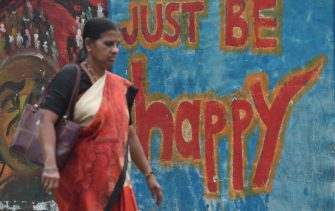 An Indian woman walks past wall graffiti in Mumbai on March 16, 2018.  The annual World Happiness Report 2018? by United Nations Sustainable Development Solutions Network released this week puts India at a lowly 133 on the list of 156 countries. The Report is a landmark survey of the state of global happiness and ranks 156 countries by their happiness levels, and 117 countries by the happiness of their immigrants. / AFP PHOTO / Indranil MUKHERJEE        (Photo credit should read INDRANIL MUKHERJEE/AFP via Getty Images)