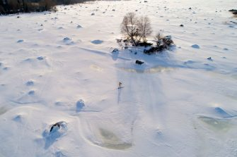 TOPSHOT - An aerial view shows a man country-skiing in Sundom aerea, near Vaasa, in the middle of the archipelago UNESCO classified, on the frozen Bothnia sea (Baltic Sea), on March 23, 2018. In the just released 2018 UN World Happiness Report, Finland took the top spot followed by its Scandinavian neighbours and Switzerland, the Netherlands, Canada, New Zealand. / AFP PHOTO / Olivier MORIN        (Photo credit should read OLIVIER MORIN/AFP via Getty Images)