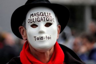 """A protester wears a mask reading """"Mask mandatory, shut your mouth"""" during a demonstration against the ongoing coronavirus Covid-19 restrictions in Liestal, near Basel, on March 20, 2021. - Between 3,000 and 5,000 people, some of them wearing white suits, take part in a 'silent demonstration on March 20, 2021 in Liestal, Northern Switzerland, demanding an end to restrictions designed to contain the Covid-19 pandemic. (Photo by STEFAN WERMUTH / AFP) (Photo by STEFAN WERMUTH/AFP via Getty Images)"""