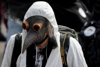 A protester smokes through a personalised mask during a demonstration against the ongoing coronavirus Covid-19 restrictions in Liestal, near Basel, on March 20, 2021. - Between 3,000 and 5,000 people, some of them wearing white suits, take part in a 'silent demonstration on March 20, 2021 in Liestal, Northern Switzerland, demanding an end to restrictions designed to contain the Covid-19 pandemic. (Photo by STEFAN WERMUTH / AFP) (Photo by STEFAN WERMUTH/AFP via Getty Images)