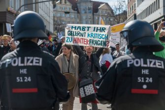 """KASSEL, GERMANY - MARCH 20: People gather to protest against ongoing lockdown measures during the third wave of the coronavirus pandemic on March 20, 2021 in Kassel, Germany. Activists from a wide range of ideologies have come from across Germany to protest for what organizers hail as """"freedom, peace and democracy."""" Germany has large numbers of very vocal coronavirus skeptics who see lockdown measures as governmental tyranny. The movement attracts, among others, mystics, QAnon and other conspiracy theorists and neo-Nazis. (Photo by Thomas Lohnes/Getty Images)"""