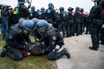 """KASSEL, GERMANY - MARCH 20: Police officers take away a woman to record his personal details as they break up a demonstration on March 20, 2021 in Kassel, Germany. Over 10.000 people gathered before to protest against ongoing lockdown measures during the third wave of the coronavirus pandemic Activists from a wide range of ideologies have come from across Germany to protest for what organizers hail as """"freedom, peace and democracy."""" Germany has large numbers of very vocal coronavirus skeptics who see lockdown measures as governmental tyranny. The movement attracts, among others, mystics, QAnon and other conspiracy theorists and neo-Nazis. (Photo by Thomas Lohnes/Getty Images)"""