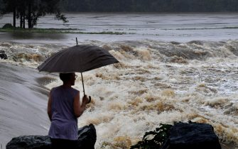 epa09089199 A man stands in front of swollen Coomera River at Oxenford Weir on the Gold Coast, Australia, 22 March 2021. The weather bureau is warning of potentially life-threatening conditions from torrential rain and storms in southern Queensland.  EPA/DAVE HUNT AUSTRALIA AND NEW ZEALAND OUT