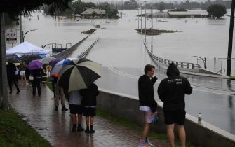 epa09089236 Onlookers watch the submerged New Windsor Bridge at Windsor in the north west of Sydney, Australia, 22 March 2021. Thousands of residents are fleeing their homes as schools are shut, and scores of people have been rescued as NSW is hit by once-in-a-generation flooding.  EPA/DEAN LEWIN AUSTRALIA AND NEW ZEALAND OUT