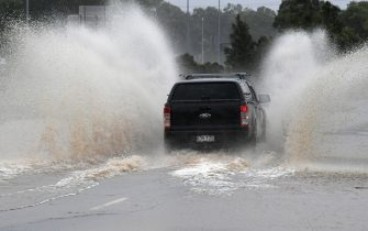epa09089239 A vehicle travels over a flooded causeway  on the Gold Coast, Australia, 22 March 2021.  The weather bureau is warning of potentially life-threatening conditions from torrential rain and storms in southern Queensland.  EPA/DAVE HUNT  AUSTRALIA AND NEW ZEALAND OUT