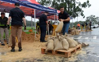 epa09087407 Rapid Relief Team (RRT) members are seen preparing sandbags in Penrith, New South Wales, Australia, 21 March 2021. Rivers are bursting their banks, dams are overflowing and many New South Wales residents are on standby to leave their homes as heavy rain continues to pelt the state.  EPA/BIANCA DE MARCHI  AUSTRALIA AND NEW ZEALAND OUT
