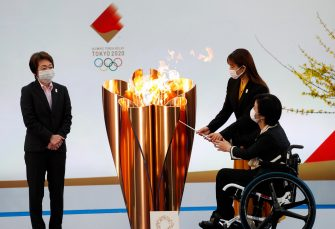 epa09095165 Tokyo 2020 Organising Committee President Seiko Hashimoto (L) looks on as actor Satomi Hishihara (R,back) and Paralyimpian Aki Taguchi light the celebration cauldron on the first day of the Tokyo 2020 Olympic torch relay in Naraha, Fukushima prefecture, Japan, 25 March 2021.  EPA/KIM KYUNG-HOON / POOL