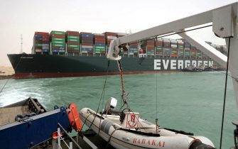 """epa09095681 A handout photo made available by the Suez Canal Authority, shows the Ever Given container ship in the Suez Canal, Egypt, 25 March 2021. the Ever Given, a large container ship ran aground in the Suez Canal on 23 March, blocking passage of other ships and causing a traffic jam for cargo vessels.  The head of the Suez Canal Authority announced on 25 March that """"the navigation through the Suez Canal is temporarily suspended"""" until the floatation of the Ever Given is completed. Its floatation is being carried out by 8 large tugboats that are towing and pushing the grounding vessel.  EPA/SUEZ CANAL AUTHORITY/HO EDITORIAL USE ONLY NO SALES HANDOUT EDITORIAL USE ONLY/NO SALES"""