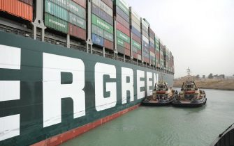 """epa09095675 A handout photo made available by the Suez Canal Authority, shows the Ever Given container ship in the Suez Canal, Egypt, 25 March 2021. the Ever Given, a large container ship ran aground in the Suez Canal on 23 March, blocking passage of other ships and causing a traffic jam for cargo vessels.  The head of the Suez Canal Authority announced on 25 March that """"the navigation through the Suez Canal is temporarily suspended"""" until the floatation of the Ever Given is completed. Its floatation is being carried out by 8 large tugboats that are towing and pushing the grounding vessel.  EPA/SUEZ CANAL AUTHORITY/HO EDITORIAL USE ONLY NO SALES HANDOUT EDITORIAL USE ONLY/NO SALES"""