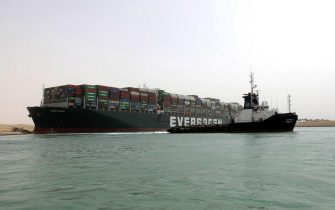 """epa09095734 A handout photo made available by the Suez Canal Authority, shows the Ever Given container ship (L) in the Suez Canal, Egypt, 25 March 2021. the Ever Given, a large container ship ran aground in the Suez Canal on 23 March, blocking passage of other ships and causing a traffic jam for cargo vessels.  The head of the Suez Canal Authority announced on 25 March that """"the navigation through the Suez Canal is temporarily suspended"""" until the floatation of the Ever Given is completed. Its floatation is being carried out by 8 large tugboats that are towing and pushing the grounding vessel.  EPA/SUEZ CANAL AUTHORITY/HO EDITORIAL USE ONLY NO SALES HANDOUT EDITORIAL USE ONLY/NO SALES"""