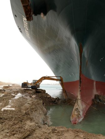 """epa09095768 A handout photo made available by the Suez Canal Authority, shows the Ever Given container ship  which ran agorund in the Suez Canal, Egypt, 25 March 2021. the Ever Given, a large container ship ran aground in the Suez Canal on 23 March, blocking passage of other ships and causing a traffic jam for cargo vessels.  The head of the Suez Canal Authority announced on 25 March that """"the navigation through the Suez Canal is temporarily suspended"""" until the floatation of the Ever Given is completed. Its floatation is being carried out by 8 large tugboats that are towing and pushing the grounding vessel.  EPA/SUEZ CANAL AUTHORITY/HO EDITORIAL USE ONLY NO SALES HANDOUT EDITORIAL USE ONLY/NO SALES"""