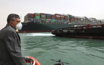 """epa09095794 A handout photo made available by the Suez Canal Authority, shows the head of the Suez Canal Authority Lt. Gen. Ossama Rabei (L) assessing the situation near the Ever Given container ship and a tugboat, in the Suez Canal, Egypt, 25 March 2021. The Ever Given, a large container ship ran aground in the Suez Canal on 23 March, blocking passage of other ships and causing a traffic jam for cargo vessels.  The head of the Suez Canal Authority announced on 25 March that """"the navigation through the Suez Canal is temporarily suspended"""" until the floatation of the Ever Given is completed. Its floatation is being carried out by 8 large tugboats that are towing and pushing the grounding vessel.  EPA/SUEZ CANAL AUTHORITY/HO EDITORIAL USE ONLY NO SALES HANDOUT EDITORIAL USE ONLY/NO SALES"""
