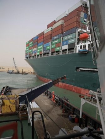 """epa09095820 A handout photo made available by the Suez Canal Authority, shows  the Ever Given container ship, in the Suez Canal, Egypt, 25 March 2021. The Ever Given, a large container ship ran aground in the Suez Canal on 23 March, blocking passage of other ships and causing a traffic jam for cargo vessels.  The head of the Suez Canal Authority announced on 25 March that """"the navigation through the Suez Canal is temporarily suspended"""" until the floatation of the Ever Given is completed. Its floatation is being carried out by 8 large tugboats that are towing and pushing the grounding vessel.  EPA/SUEZ CANAL AUTHORITY/HO EDITORIAL USE ONLY NO SALES HANDOUT EDITORIAL USE ONLY/NO SALES"""