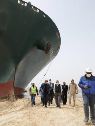 """epa09095775 A handout photo made available by the Suez Canal Authority, shows officials and workers assessing the situation near the Ever Given container ship  which ran agorund in the Suez Canal, Egypt, 25 March 2021. the Ever Given, a large container ship ran aground in the Suez Canal on 23 March, blocking passage of other ships and causing a traffic jam for cargo vessels.  The head of the Suez Canal Authority announced on 25 March that """"the navigation through the Suez Canal is temporarily suspended"""" until the floatation of the Ever Given is completed. Its floatation is being carried out by 8 large tugboats that are towing and pushing the grounding vessel.  EPA/SUEZ CANAL AUTHORITY/HO EDITORIAL USE ONLY NO SALES HANDOUT EDITORIAL USE ONLY/NO SALES"""