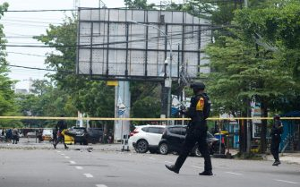 epa09102556 Police counter-terrorism squad members cordon off the area surrounding the Sacred Heart of Jesus Cathedral in the aftermath of an explosion, in Makassar, South Sulawesi, Indonesia, 28 March 2021. At least nine people were wounded as a suspected suicide bomber blew themselves up outside the church on Palm Sunday. The number of casualties was still unclear.  EPA/IQBAL LUBIS