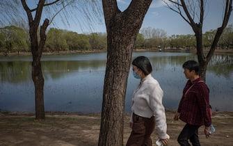 epa09104887 People walk in a park in Beijing, China, 29 March 2021.  EPA/ROMAN PILIPEY