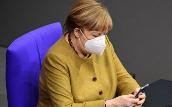 epa09050597 German Chancellor Angela Merkel looks on her phone during a session at the German parliament Bundestag in Berlin, Germany, 04 March 2021. Members of the German parliament Bundestag discussed the ongoing COVID-19 pandemic situation in the country one day after new lockdown measures and opening scenarios were resolved.  EPA/CLEMENS BILAN