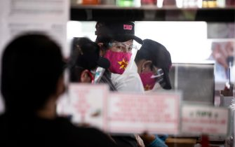 epa09045549 Employees wearing masks prepare the orders at Pink's Hot Dog as the restaurant reopens for pick-up and outdoor dining in Hollywood, California, USA, 01 March 2021. Pink's closed its doors for the past two months due to the increase in numbers of coronavirus cases concerned about the Covid-19 surge in order to keep patrons and staff safe.  EPA/ETIENNE LAURENT