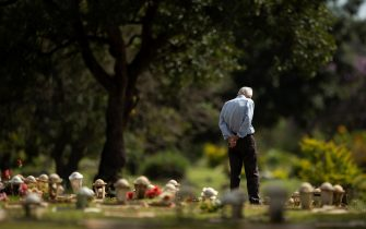 epa09099730 A man visits a tomb in the cemetery Campo de Esperanza, in Brasilia, Brazil, 26 March 2021. Brazil joined the club of the nations producing its own vaccine against Covid-19, in order to confront the Covid-19 pandemic that has come to kill a person every half a minute in Brazil.  EPA/Joedson Alves