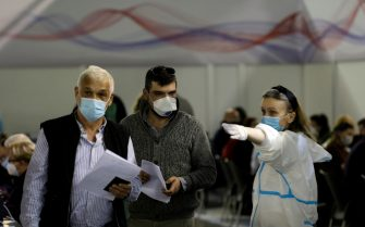 epa09100833 A medical worker directs patients that have come to receive a dose of AstraZeneca vaccine at the Belgrade Fair vaccination center in Belgrade, Serbia, 27 March 2021. Thousands of vaccine-seekers from neighboring countries like Bosnia and Herzegovina, North Macedonia and Montenegro have crowded the Belgrade's main vaccination center after Serbian authorities offered free coronavirus jabs for foreigners if they show up over the weekend.  EPA/ANDREJ CUKIC