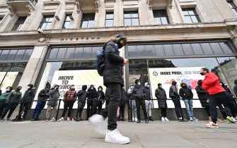 Shoppers queue outside a Nike store in central London as coronavirus restrictions are eased across the country on April 12, 2021. (Photo by Glyn KIRK / AFP) (Photo by GLYN KIRK/AFP via Getty Images)