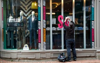 A worker removes a 'Sale' sign from the window of a Suit Direct store in Birmingham, U.K., on Monday, April 12, 2021. Non-essential retailers as well as pubs and restaurants with outdoor space will reopen Monday across England after almost 100 days of lockdown, hoping pent-up demand will translate into strong sales. Photographer: Darren Staples/Bloomberg via Getty Images