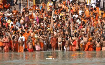 epa09130298 Indian holy men or Naga Sadhu along with the other pilgrims perform the rituals as they take the holy dip in Ganga river during the Kumbh Mela royal bath m(Sacred Hindu Pilgrimage) at Haridwar, Uttarakhand, India, 12 April 2021. Thousands of pilgrims are gathering and taking holy dip in Kumbh Mela that is a mass Hindu pilgrimage which occurs after every twelve years and rotates among four locations Prayag (Allahabad) at the confluence of the Ganga and Yamuna and mythical Saraswati river, Haridwar along the Ganga river, Ujjain along the Kshipra river and Nashik along the Godavari river.  EPA/IDREES MOHAMMED  EPA-EFE/IDREES MOHAMMED