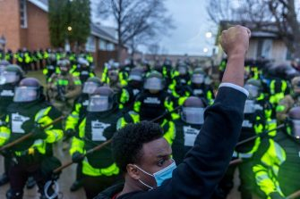 A man raises his fist as he faces the Minnesota State Troopers standing guard outside the Brooklyn Center Police Station after a police officer shot and killed 20-year-old Daunte Wright during a traffic stop in Brooklyn Center, Minneapolis, Minnesota on April 12, 2021. - Fresh protests broke out Tuesday night in Minneapolis despite a curfew implemented after a police officer fatally shot a young Black man when she appeared to confuse her handgun with her taser, fueling tensions in a US city already on edge because of the George Floyd murder trial. Shortly before 9:00 pm local time (0200GMT Tuesday), nearly two hours after the curfew went into effect, dozens of protesters continued to wave signs and chant slogans in front of the police station in Brooklyn Center, where Sunday's killing occurred. (Photo by Kerem Yucel / AFP) (Photo by KEREM YUCEL/AFP via Getty Images)