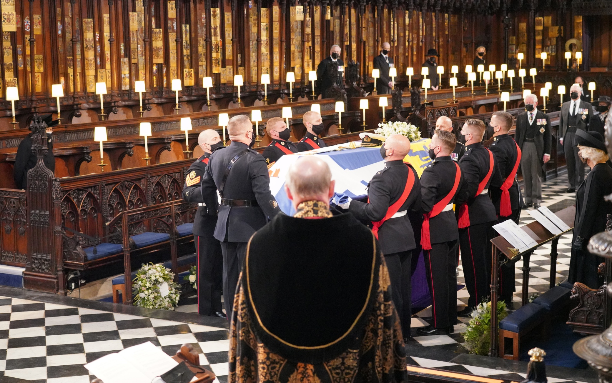 Queen Elizabeth II (left) watches as pall bearers carry the coffin of the Duke of Edinburgh during his funeral at St George's Chapel, Windsor Castle, Berkshire. Picture date: Saturday April 17, 2021.