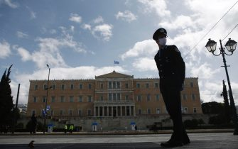 epa08321040 A police officer wearing protective gloves stands guard in front of the parliament building as presidential guards perform during a ceremony marking Greece's Independence Day, at the Tomb of the Unknown Soldier at central Syntagma Square in Athens, Greece, 25 March 2020. In 1821 the Greeks fought the Ottoman Turks as their enemy, President of the Hellenic Republic Katerina Sakellaropoulou said on Tuesday, but today they fight against the coronavirus pandemic.  EPA/YANNIS KOLESIDIS
