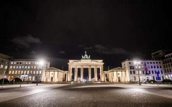 epa09112663 The deserted Pariser Platz square at nighttime in front of the Brandenburg Gate in Berlin, Germany, 02 April 2021. Due to rising Coronavirus infection numbers, since Good Friday, 02 April 2021, a nightly curfew between 09.00 o clock PM and 05.00 o clock AM has been decreed in Berlin, where a maximum of two persons are allowed to linger in public places.  EPA/CLEMENS BILAN