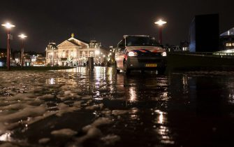 epa09016975 A police car parked on the Museumplein, in Amsterdam, The Netherlands, 16 February 2021. The court of appeal in The Hague has suspended the court's decision in summary proceedings about the lifting of the curfew upon the request of the Government, which has appealed against the verdict. The curfew will remain in effect for the time being.  EPA/MARCO DE SWART