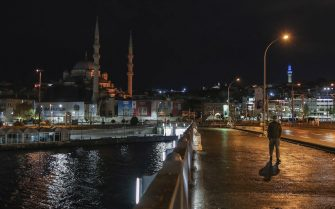 epa08834800 A man walk on the Galata bridge backdropped by the New Eminonu Mosque during a curfew in Istanbul, Turkey, 21 November 2020. The Turkish government has introduced partial curfews and other measures to curb increasing COVID-19 cases in the country, while health experts call for a full lockdown and more transparency in pandemic data. Starting 20 November evening, the Turkish government imposed partial weekend curfews between 10 a.m. and 8 p.m. on most citizens. People under 20 and over 65 will be allowed to be outdoors during specific hours on weekdays while cafes and restaurants will be closed for costumers on weekends.  EPA/ERDEM SAHIN