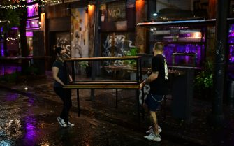 Employees of a bar enter a table to close the bar located in Serrano square in Buenos Aires, on April 8, 2021. - Argentina's President Alberto Fernandez announced on Wednesday, April 7, a three-week nighttime curfew after a second consecutive day of record coronavirus infections. (Photo by RONALDO SCHEMIDT / AFP) (Photo by RONALDO SCHEMIDT/AFP via Getty Images)