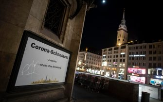 epa09157607 A sign advertises a Corona rapid test station in the pedestrian zone before curfew in the city center in Munich, Bavaria, Germany, 24 April 2021. A so-called 'emergency brake' has taken effect in Germany on 24 April, which includes curfew restrictions from 10 p.m. to 5 a.m. in regions with increased coronavirus incidence.  EPA/LUKAS BARTH-TUTTAS