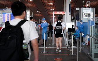 Travellers walk through a temperature monitoring device at Beijing's international airport on June 17, 2020. - Beijing's airports cancelled more than 1,200 flights and schools in the Chinese capital were closed again on June 17 as authorities rushed to contain a new coronavirus outbreak linked to a wholesale food market. (Photo by STR / AFP)