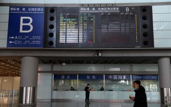 (FILES) This file photo taken on March 27, 2020 shows people standing below a board showing international arrivals, in the empty arrivals area at Beijing Capital Airport. - Beijing cancelled at least 1,255 scheduled inbound and outbound flights on June 17, 2020 as fears grow over a new virus outbreak, affecting nearly 70 per cent of all trips, reported the state-run media. (Photo by GREG BAKER / AFP)