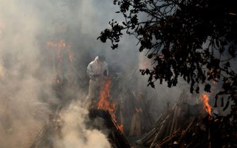 A relative stands next to the burning funeral pyres of those who died due to the coronavirus disease (COVID-19), at Ghazipur cremation ground in New Delhi. In India the highest single-day spike in coronavirus infection. The report recorded 352,991 new Covid-19 cases and 2,812 deaths in the last 24 hours amid an oxygen crisis. - Naveen Sharma / SOPA Images//SOPAIMAGES_08380019/2104270904/Credit:SOPA Images/SIPA/2104270907
