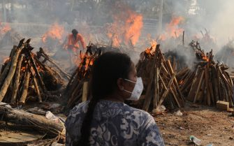 A family member looks on as several funeral pyres of those patients who died of COVID-19 disease burn up during the mass cremation at Ghazipur cremation ground in New Delhi. In India the highest single-day spike in coronavirus infection. The report recorded 352,991 new Covid-19 cases and 2,812 deaths in the last 24 hours amid an oxygen crisis. - Naveen Sharma / SOPA Images//SOPAIMAGES_08380023/2104270905/Credit:SOPA Images/SIPA/2104270907